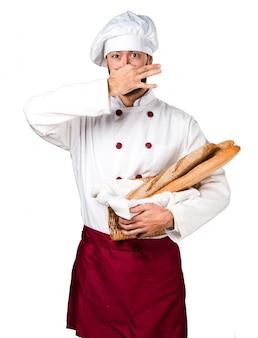 Junger bäcker hält etwas brot und macht riechende schlechte geste
