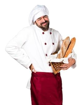 Junger bäcker hält etwas brot und mit rückenschmerzen