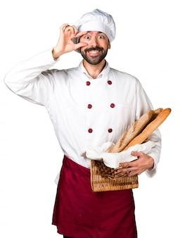 Junger bäcker hält etwas brot und zeigt etwas