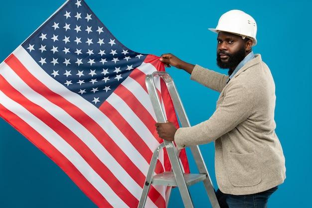 Junger bärtiger afroamerikanischer arbeiter im schutzhelm und in der formellen kleidung, die auf trittleiter stehen und us-flagge halten