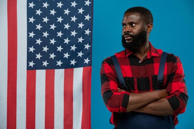 Junger bärtiger afroamerikanischer arbeiter in flanell und overall, dessen arme von der brust verschränkt sind und die gegen den sternenbanner-copyspace stehen