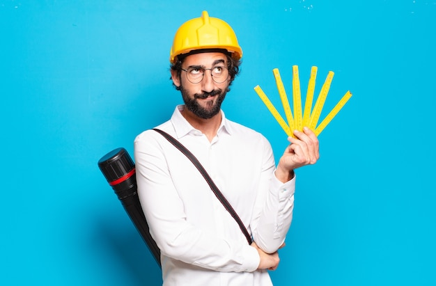 Junger bärtiger architekt mit gelbem helm