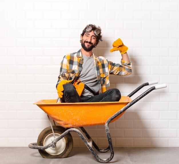 Junger bärtiger bauarbeiter mann auf einer schubkarre