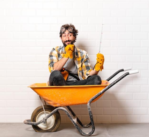 Junger bärtiger bauarbeitermann auf einer schubkarre