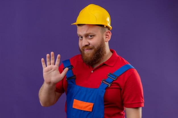 Junger bärtiger baumeistermann in bauuniform und sicherheitshelm mit skeptischem ausdruck, der mit den fingern nummer fünf über lila hintergrund zeigt und zeigt