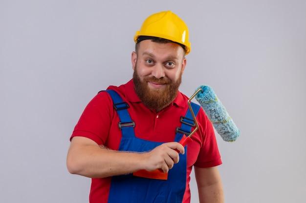 Junger bärtiger baumeistermann in der bauuniform und im sicherheitshelm, der farbroller hält kamera glücklich und positiv lächelnd 2 betrachtet