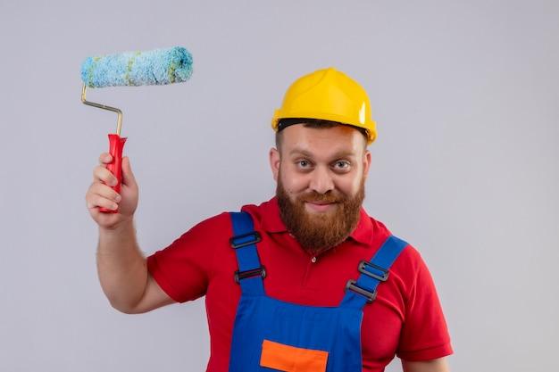 Junger bärtiger baumeistermann in der bauuniform und im sicherheitshelm, der farbroller hält kamera glücklich und positiv lächelnd betrachtet