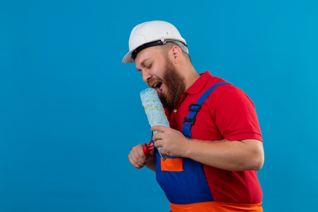 Junger bärtiger baumeistermann in der bauuniform und im sicherheitshelm, der farbroller verwendet, der als mikrofon singt und spaß bei der arbeit hat