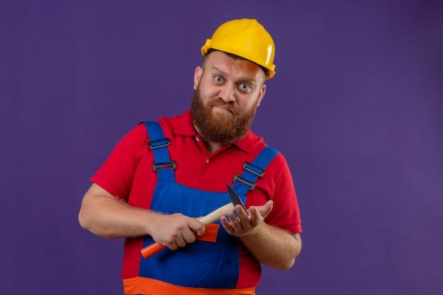 Junger bärtiger baumeistermann in der bauuniform und im sicherheitshelm, der hammer mit stirnrunzeln über lila hintergrund hält