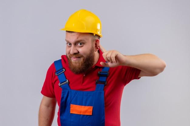 Junger bärtiger baumeistermann in der bauuniform und im sicherheitshelm, der kamera betrachtet, die hand nahe ohr hält, das versucht, zuzuhören