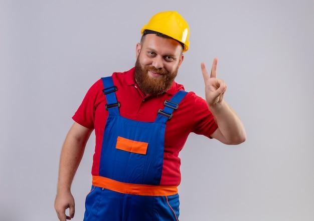 Junger bärtiger baumeistermann in der bauuniform und im sicherheitshelm, der kamera lächelnd zeigt und mit den fingern nummer zwei oder siegeszeichen oben zeigt