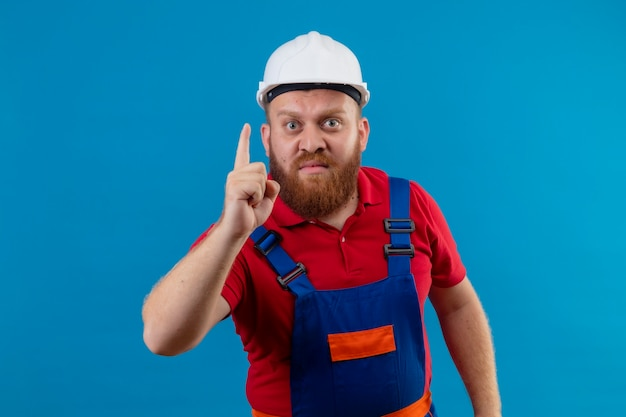 Junger bärtiger baumeistermann in der bauuniform und im sicherheitshelm, der kamera missfiel, zeigt finger nach oben, warnung vor gefahr
