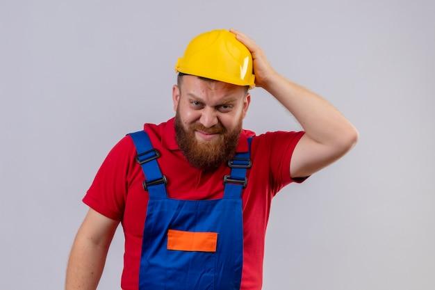Junger bärtiger baumeistermann in der bauuniform und im sicherheitshelm, der kamera verwirrt und sehr besorgt mit hand auf kopf für fehler betrachtet