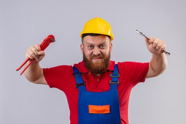 Junger bärtiger baumeistermann in der bauuniform und im sicherheitshelm, der verstellbare schraubenschlüssel in den erhobenen händen hält, die kamera mit aggressivem ausdruck betrachten