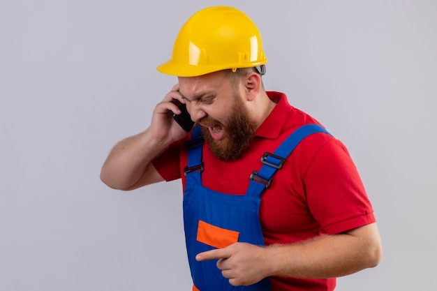 Junger bärtiger baumeistermann in der bauuniform und im sicherheitshelm, die schreien, während auf handy mit aggressivem ausdruck sprechen