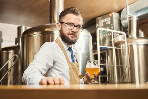 Junger bärtiger brauer, der kamera betrachtet und lächelt, während glas des goldenen bieres in der hand hält. mann, der weißes hemd und schürze trägt, die in der brauerei stehen und bier untersuchen. konzept der produktion.