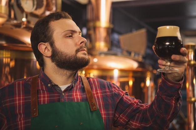 Junger bärtiger brauer, der schürze trägt, die in seiner brauerei arbeitet und dunkles bier in einem glas untersucht