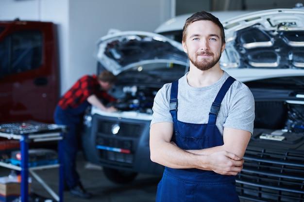 Junger bärtiger erfolgreicher reparaturmann des autoservicezentrums
