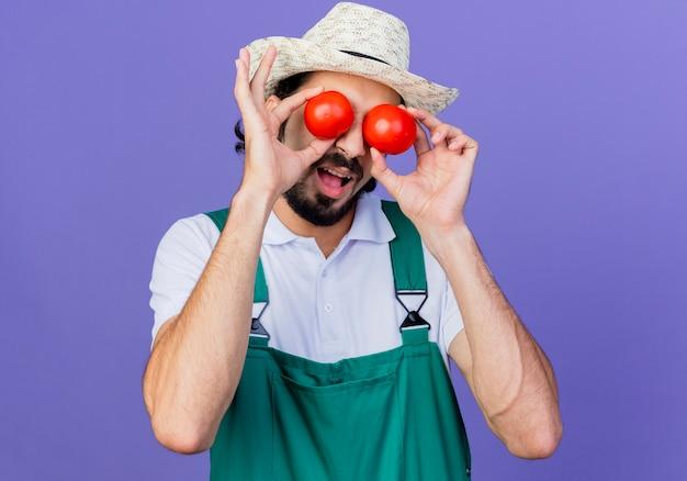 Junger bärtiger gärtnermann, der overall und hut hält, der frische tomaten bedeckt, die augen mit ihnen lächelnd über blauer wand stehend halten