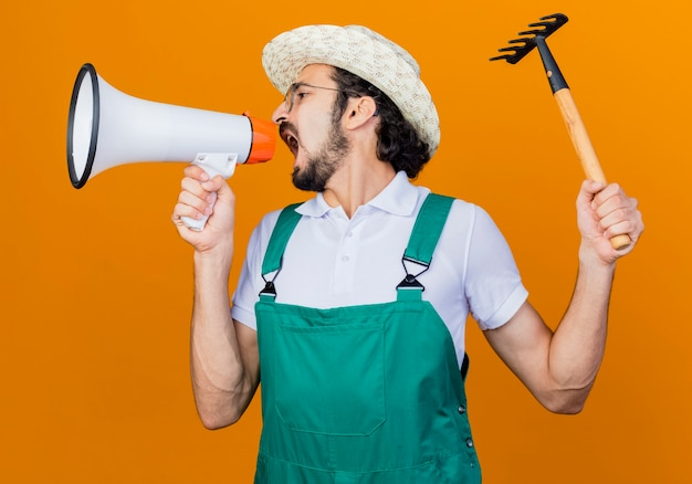 Junger bärtiger gärtnermann, der overall und hut hält, der mini-rechen hält, der zum megaphon schreit, das wütend ist, über orange wand stehend