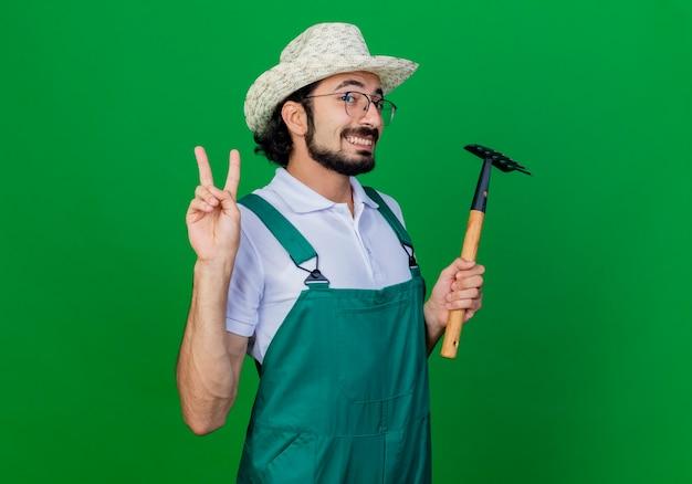 Junger bärtiger gärtnermann, der overall und hut hält, der mini-rechen lächelnd zeigt v-zeichen