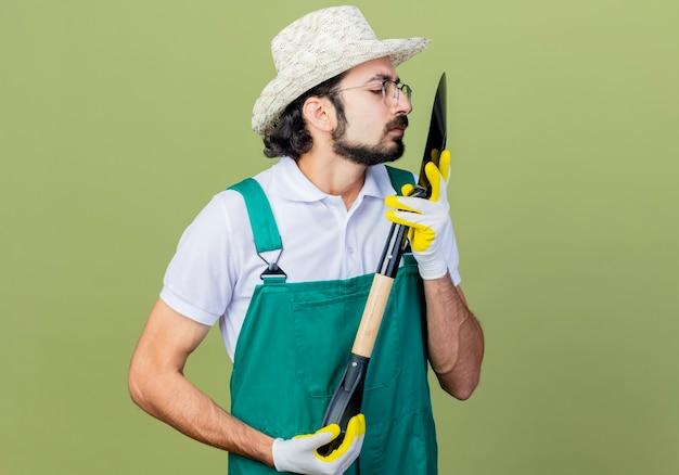 Junger bärtiger gärtnermann, der overall und hut hält, der schaufel hält, der sie eng über hellgrüner wand stehend betrachtet