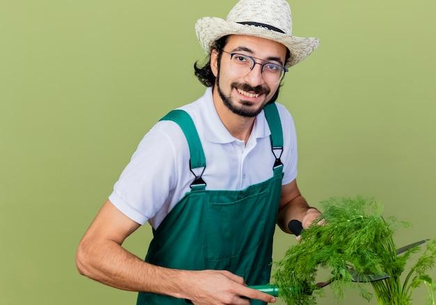 Junger bärtiger gärtnermann, der overall und hut hält, die frische kräuter betrachten, die vorne lächelnd mit glücklichem gesicht stehen über hellgrüner wand stehen