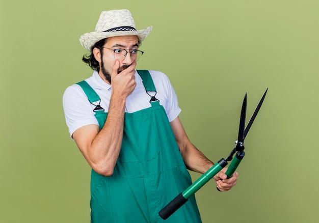 Junger bärtiger gärtnermann, der overall und hut hält, die heckenscheren hält, die überrascht und erstaunt über hellgrüne wand stehen