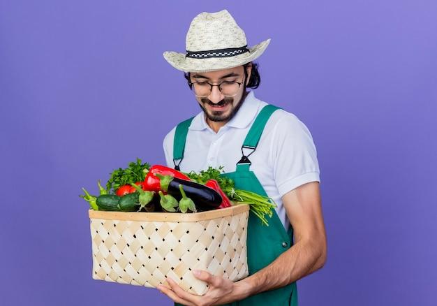 Junger bärtiger gärtnermann, der overall und hut hält kiste voll des gemüses, das lächelnd unten steht über blaue wand hält
