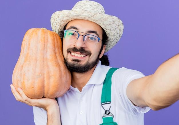 Junger bärtiger gärtnermann, der overall und hut hält kürbis, der vorne lächelnd mit glücklichem gesicht über blauer wand steht
