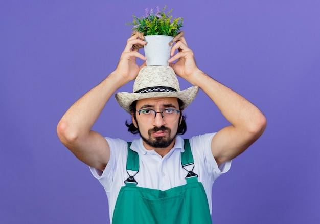 Junger bärtiger gärtnermann, der overall und hut hält topfpflanze auf seinem kopf, der vorne mit traurigem ausdruck steht, der über blauer wand steht