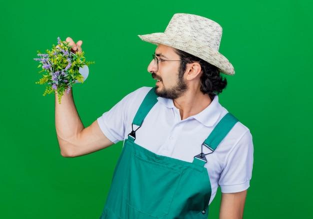 Junger bärtiger gärtnermann, der overall und hut hält topfpflanze hält, die es unzufrieden betrachtet