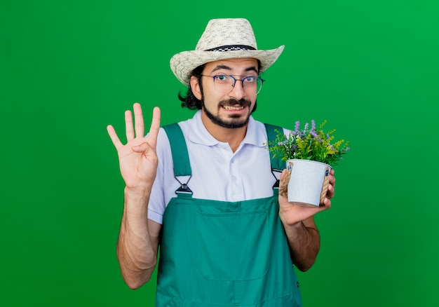 Junger bärtiger gärtnermann, der overall und hut hält topfpflanze zeigt nummer vier