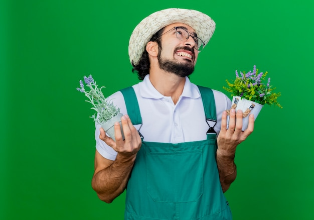 Junger bärtiger gärtnermann, der overall und hut hält topfpflanzen, die mit genervtem ausdruck nachschlagen