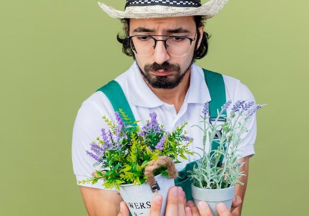 Junger bärtiger gärtnermann, der overall und hut hält topfpflanzen hält, die sie mit traurigem ausdruck betrachten, der über hellgrüner wand steht