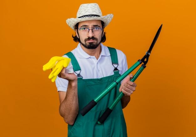 Junger bärtiger gärtnermann, der overall und hut trägt, die heckenscheren und gummihandschuhe hält, die vorne mit traurigem ausdruck stehen, der über orange wand steht
