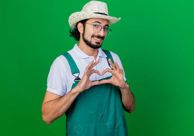 Junger bärtiger gärtnermann, der overall und hut trägt, macht herzgeste mit den fingern, die mit glücklichem gesicht lächeln