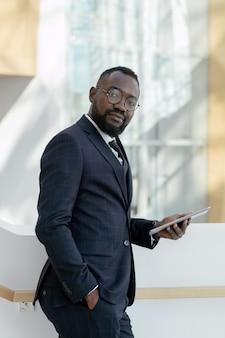 Junger bärtiger geschäftsmann in brillen und abendkleidung mit digitalem tablet