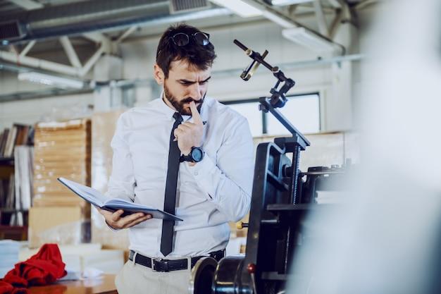 Junger bärtiger grafiker mit brille, die notizbuch hält und auf druckmaschine prüft