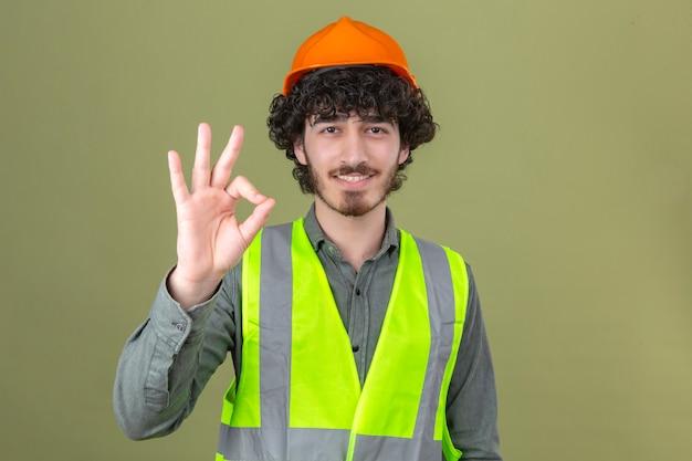 Junger bärtiger gutaussehender ingenieur, der sicherheitshelm und weste trägt, die das ok-zeichen lächelnd über isolierter grüner wand stehen