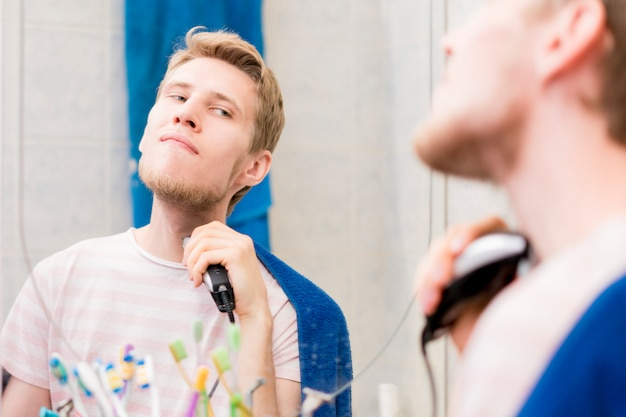 Junger bärtiger gutaussehender mann, der bart mit maschine im badezimmer schaut in einem spiegel hat