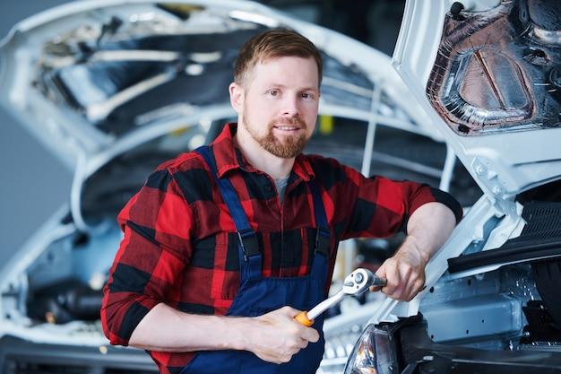 Junger bärtiger handwerker in der arbeitskleidung, die handwerkzeug hält, während er durch auto im hangar oder in der werkstatt steht