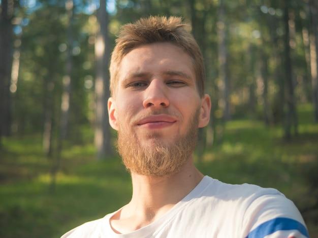 Junger bärtiger hippie-mann, der selbstporträt im wald reist in die schweiz-naturplätze nimmt