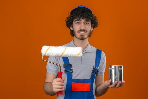 Junger bärtiger hübscher baumeister, der bauuniform und kappe hält, die farbroller und farbe hält, kann freundlich über isolierte orange wand lächeln
