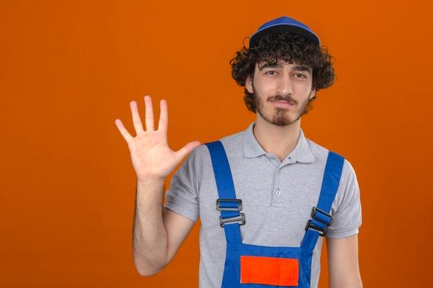 Junger bärtiger hübscher baumeister, der bauuniform und kappe trägt, die offene handfläche nummer fünf zeigt, während freundlich über isolierte orange wand lächelt