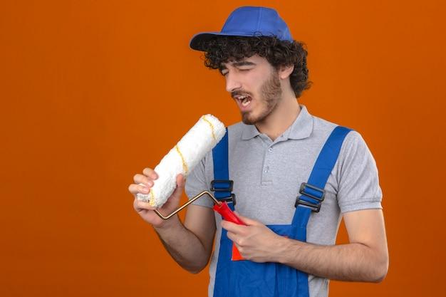 Junger bärtiger hübscher baumeister, der bauuniform und kappe unter verwendung des farbrollers als mikrofon singendes liedspaß bei der arbeit konzept über isolierte orange wand trägt