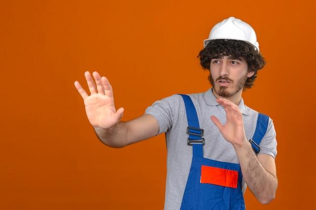 Junger bärtiger hübscher baumeister, der bauuniform und schutzhelm trägt, der seine hände hochhält und erzählt, kommt nicht näher über isolierte orange wand