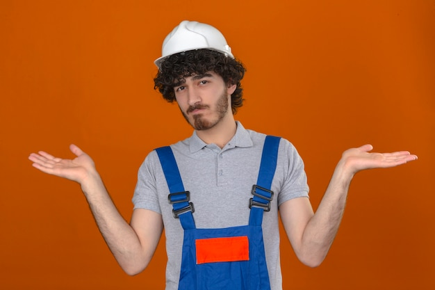 Junger bärtiger hübscher baumeister, der bauuniform und sicherheitshelm ahnungslos trägt und mit offenen armen verwechselt keine ahnung konzept steht über isolierte orange wand