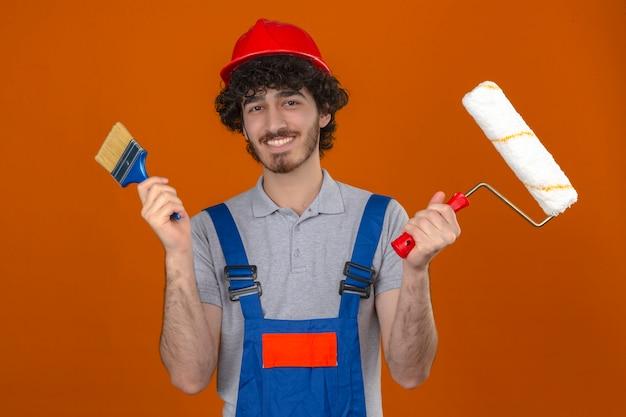 Junger bärtiger hübscher baumeister, der bauuniform und sicherheitshelm hält farbroller und pinsel in händen trägt, die glücklich über isolierte orange wand lächeln