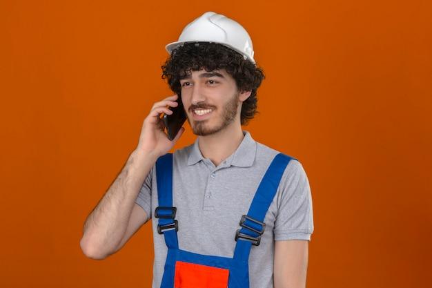 Junger bärtiger hübscher baumeister, der bauuniform und sicherheitshelm trägt, der auf handy spricht, das mit glücklichem gesicht über isolierter orange wand lächelt